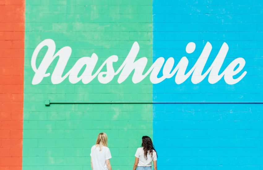 two women facing wall with nashville text
